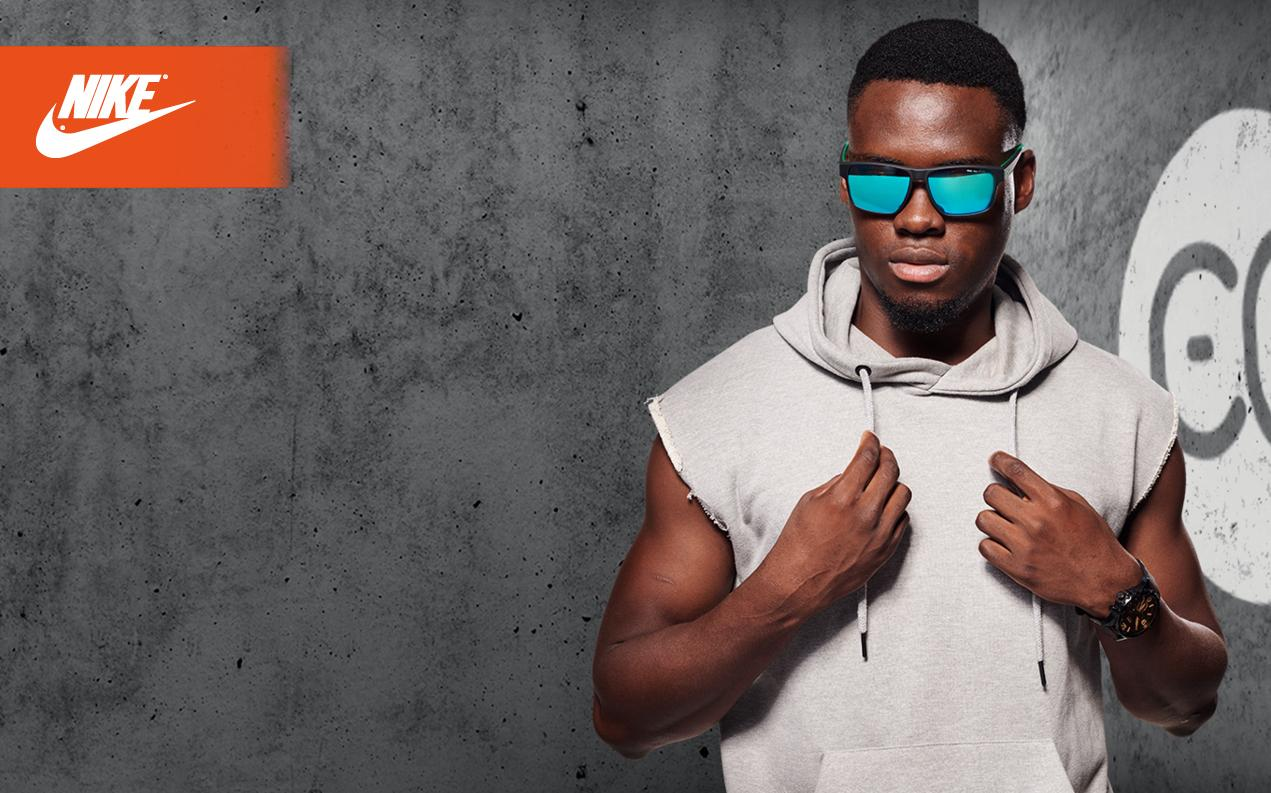 Man wearing hoodie and blue-mirrored sports glasses by Nike